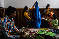 Brinda, shares a light moment while showing off her new saree in her room where she is staying during a court hearing for her legal case, in the Guria office in Varanasi, Uttar Pradesh, India on 24 November 2013. One of the 57 underaged and trafficked girls rescued from the Shivdaspur red light area in Varanasi, she has been fighting a court case against her traffickers and brothel owners for the past 8 years with the help of NGO Guria Swayam Sevi Sansthan