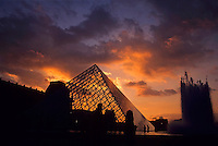 Silhouetted glass pyramid and buildings of the Musée du Louvre, Paris, France.