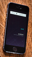 Smart Phone App called Uber, Shown on an Iphone - Jun 2014. <br /> <br /> which allows customers to book a taxi from their location using a smart phone. Black Cab Drivers claim the Uber is not regulated enough.