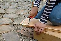 Kinder basteln sich einen Apfeltrockner, Kind sägt Schlitze in ein Seitenteil als Aufhängung für die Stäbe, Apfel, Äpfel, Äpfel trocknen, Trockenobst, Apfelringe, apple, apples