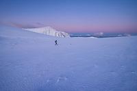 Female hiker walking across empty winter mountain landscape at dawn, Moskenesøy, Lofoten Islands, Norway