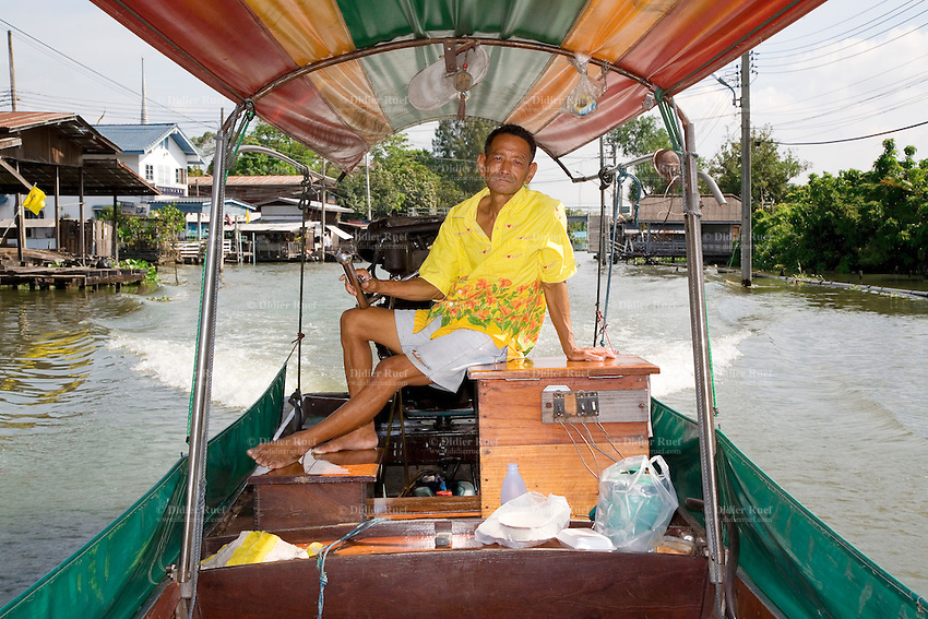 """Thailand. Bangkok. Long tail boat ride along the canal (Klong) Noi. The boat is usualy docked at a pier in Tha Tian. The long-tail boat is a type of watercraft native to Southeast Asia, which uses a common automotive engine as a readily available and maintainable powerplant. A craft designed to carry passengers on a river may include a lightweight long canoe hull, up to 30 meters, and a canopy. The sole defining characteristic is a secondhand car or truck engine. This engine is invariably mounted on an inboard turret-like pole which can rotate through 180 degrees, allowing steering by thrust vectoring. The propeller is mounted directly on the driveshaft with no additional gearing or transmission. Usually the engine also swivels up and down to provide a """"neutral gear"""" where the propeller does not contact the water. The driveshaft must be extended by several meters of metal rod to properly position the propeller, giving the boat its name and distinct appearance. Control is achieved by moving the engine with a lever stick attached to the inboard side. Ignition and throttle controls provide simple means to control this simple craft. Tha Tian is a community located in the downtown area and in the center of the urban historic district, called Koh Rattanakosin. 29.03.09 © 2009 Didier Ruef"""
