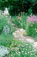 Flagstone path through pastel pinks and lavender garden with church birdhouse  entwined with clematis vine