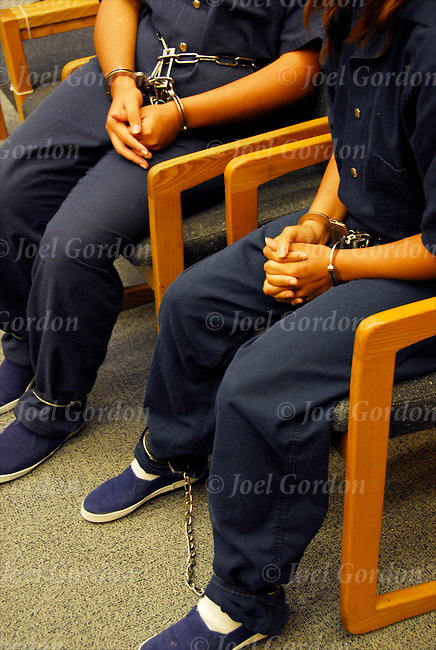 Juveniles in handcuffs and leg-irons sitting in the Juvenile Justice Center