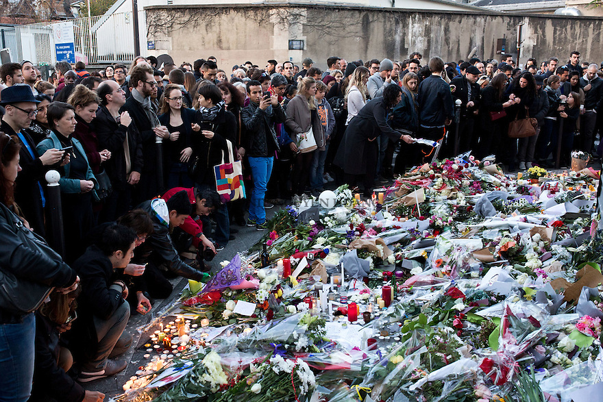 PARIS, FRANCE - NOVEMBER 15: Hundreds of people gathering in front of the restaurant le Petit Cambodge and leaving flowers, words and candles in memory of the victimes of the terrorist attacks in Paris, November 15,2015. The attacks of the 13th of November killed 129 people in Paris and injured 352.