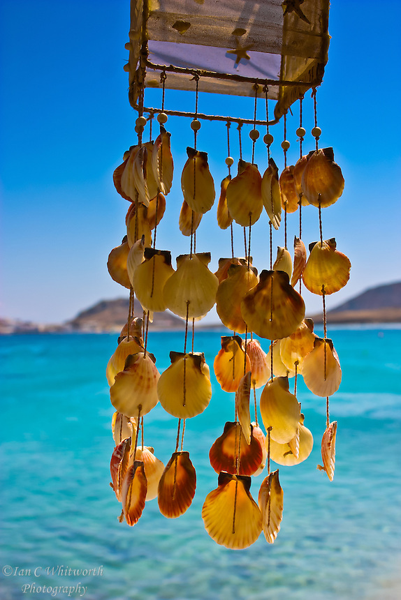 Dangling shells in a wind chime overlooking the water at a beach in Mykonos Greece
