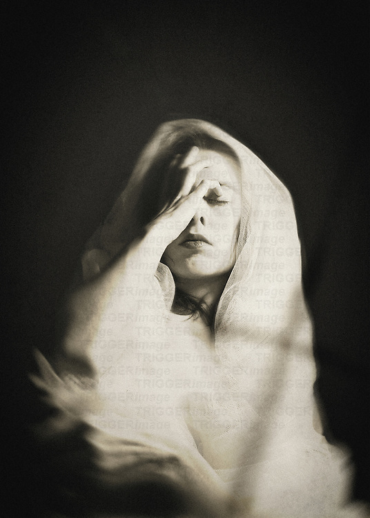 A woman in a white veil, with closed eyes and her right hand touching her forehead, with a shadow of a cross visible on the material.