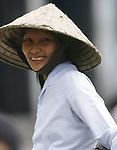 A woman smiles beneath a bamboo cone hat in Hanoi, North Vietnam.  (Jim Bryant Photo).....