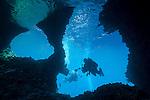 Misool, Raja Ampat, Indonesia; Boo area, two scuba divers swimming through Boo Windows