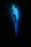 qj0489-D. scuba diver (model released) silhouetted in sheer-walled rock fissure. Poor Knights Islands Marine Reserve, New Zealand, Pacific Ocean.<br /> Photo Copyright &copy; Brandon Cole. All rights reserved worldwide.  www.brandoncole.com<br /> <br /> This photo is NOT free. It is NOT in the public domain. This photo is a Copyrighted Work, registered with the US Copyright Office. <br /> Rights to reproduction of photograph granted only upon payment in full of agreed upon licensing fee. Any use of this photo prior to such payment is an infringement of copyright and punishable by fines up to  $150,000 USD.<br /> <br /> Brandon Cole<br /> MARINE PHOTOGRAPHY<br /> http://www.brandoncole.com<br /> email: brandoncole@msn.com<br /> 4917 N. Boeing Rd.<br /> Spokane Valley, WA  99206  USA<br /> tel: 509-535-3489