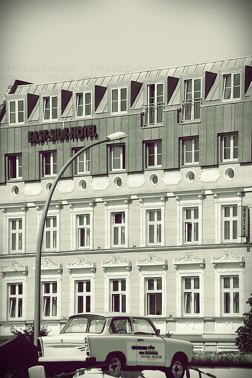 The facade of the East-Side-Hotel on the East Side Gallery with a car of the brand Trabant on the wall in Berlin.