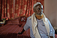 An imam sits on his bed in his house in Eyl.