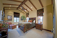 Master bedroom is seen during daytime with multiple windows and dark wood furniture