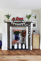 Cheerful bunting and flowers adorn this cast-iron fireplace, which serves as a reminder of the house's age