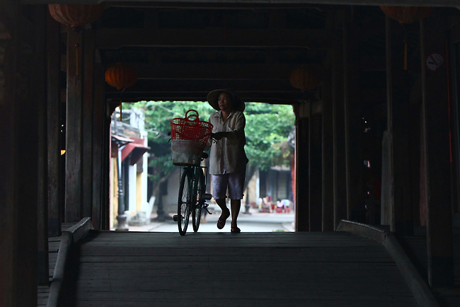 A woman walks a bicycle across the Japanese Bridge in Hoi An, Vietnam. The covered wooden structure dates from the 16th century. The city was an important  trading port from the 15th to the 19th centuries, and the architecture of Hoi An Ancient Town is the most well-preserved in Vietnam. April 22, 2012.