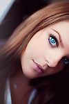 Close up of young woman with brunette hair and blue eyes looking into camera