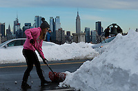 A woman shovels in the neighborhood of Weehawken while the Empire State Building and Middle Manhattan are seen on the background after the pass of the winter storm JONAS, in New York, 01/24/2016. Photo by VIEWpress