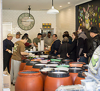 Customers line up in the Pickle Guys store in the Lower East Side of New York on Sunday, April 2, 2017 to buy freshly ground horseradish and pickles for Passover. Everyone from millennials to former Lower East Sider's descend on the store to buy the freshly ground pungent horseradish to enjoy and to use in Passover seders. The bitter herb brings tears to our eyes and reminds us of the tribulations afflicted on the Jewish people in their flight from Egypt. Passover begins the evening of April 10.  (© Richard B. Levine)