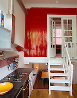 A small split-level apartment has a kitchen on the middle level with a dining area below and an living room above it behind a glossy red wall