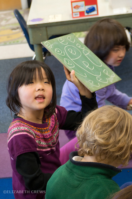 """Berkeley CA Kindergarten student, Aian, showing off ability to write letter """"E"""""""