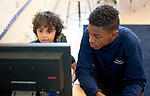 WATERBURY,  CT-051617JS05- Joseph Rodriguez,13,  a member of the Duggan School student council, helps kindergarden student Trayce Richmond as they work on problem solving programs on one of the class computers during school on Tuesday. Jim Shannon Republican-American