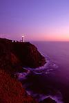 Northhead Ilwaco lighthouse at sunset along the Washington coastline Pacific ocean with rocks and cliff near Ilwaco Washington State USA.