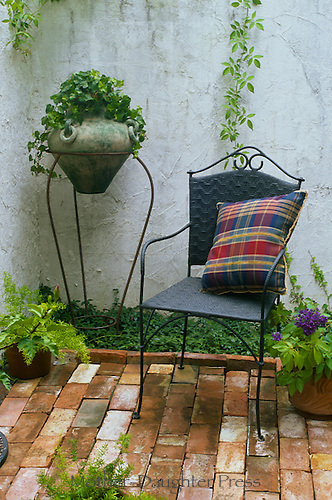 Brick patio with wrought iron furniture and potted plants vertical
