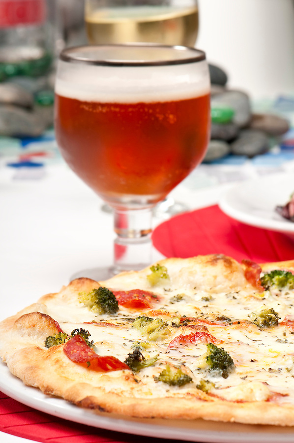 Plate of pizza with glass of beer in the background with copyspace
