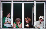 Women watch Savannah's  St. Patrick's Day Parade from a second-floor window.