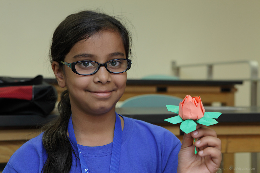 Zainab Khokha holds a modular origami flower she has foldd in a class at the OrigamiUSA 2014 convention.