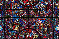 Medieval stained glass Window of the Gothic Cathedral of Chartres, France - dedicated to The life of St Lubin. Centre bottom panel - Signature panel (Wine cryers). Above left - Procession; a nobleman and his retinue, above right - Procession; a group of laymen and clerics departing from a church. Top left -  The young Lubin working as a shepherd, top right - A monk gives Lubin a belt with the alphabet written on it. A UNESCO World Heritage Site.  .