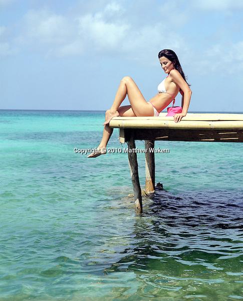 Woman in bikini sitting on bamboo dock over ocean water