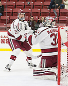 Wiley Sherman (Harvard - 25) and Merrick Madsen (Harvard - 31) keep their eyes on the airborne puck. - The Harvard University Crimson defeated the visiting Rensselaer Polytechnic Institute Engineers 5-2 in game 1 of their ECAC quarterfinal series on Friday, March 11, 2016, at Bright-Landry Hockey Center in Boston, Massachusetts.
