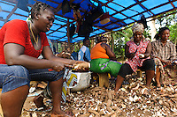 Woman processing cassava at a small factory run by Planting Promise, Newton, Freetown, Sierra Leone. Planting Promise is an organization dedicated to the development of education in Sierra Leone. Its aim is to bring opportunities to initiate self-run, self-supporting projects that offer real solutions to the difficulties facing the world's poorest country. They believe real and lasting development comes from below, from local projects that address specific needs, rather than large international models. To this end, they currently run five projects that aim to bring wealth into the country through business. The profits from these businesses are then used to support free education for children and adults...Through the combination of business with social progress, the charity hopes that they are providing real, lasting and profound changes for the better, by promoting sustainable and beneficial industry in the country, and putting it to the service to the needs of the people. As well as providing the income to fund the school, the farms will also be an example of successful commercial enterprise to teach the children in the school the viability of profit-making schemes that go beyond subsistence models, the only things the children of these desperately poor areas are accustomed to. By learning particular details of the challenges that they will face, the children will emerge from this school equipped to contribute in a real way to their society.