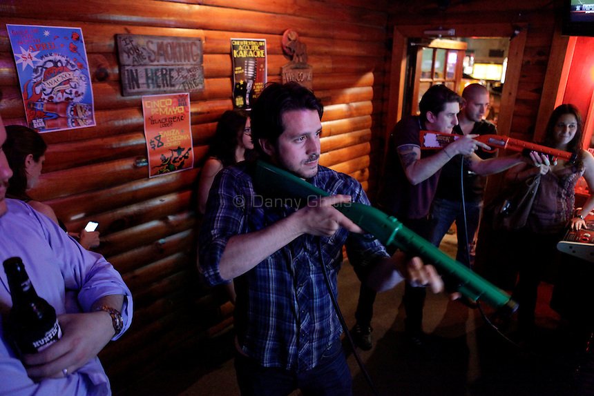 Reigning Big Buck world champion Alex DerHohannesian, 30, plays at The Black Bear Lodge in Manhattan, which hosted an official Big Buck Party on Thursday April, 28, 2011. Fans of the popular hunting arcade game were invited to test their skill against other Big Buck Hunter fans to compete for prizes, enter to win raffle merchandise and meet Big Buck Girls...Danny Ghitis for The New York Times