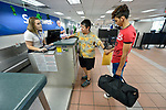 Edwin Chacon, an asylum seeker from Honduras, checks in for a flight at the Valley International Airport in Harlingen, Texas, with help from Cindy Johnson, a United Methodist deaconess. Johnson helps transport immigrants on behalf of the Posada Providencia in San Benito, where Chacon, 18, stayed for several days after being released by immigration authorities pending a judicial hearing on his asylum request. He was on his way to stay with a relative elsewhere in the United States.<br /> <br /> Sponsored by the Catholic Sisters of Divine Providence, the Posada Providencia provides a safe place for people in crisis from all over the world who are seeking legal refuge in the United States.