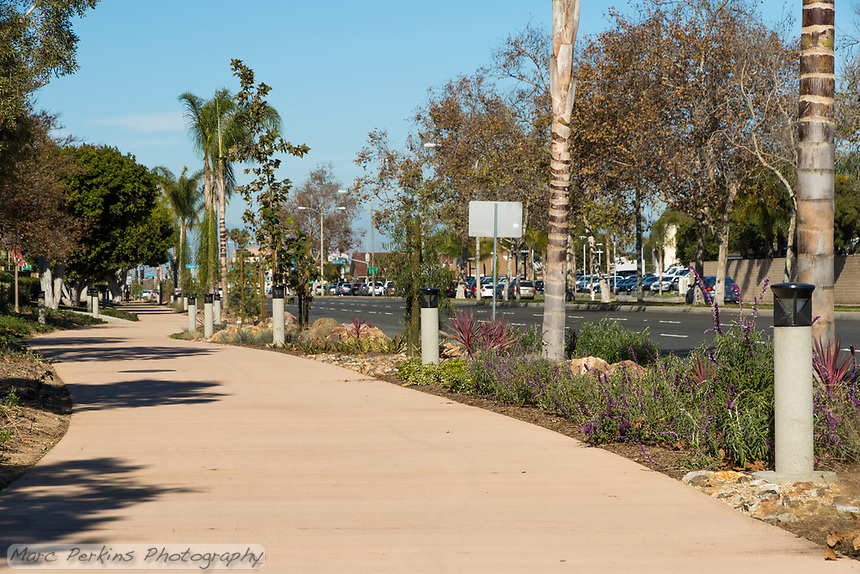 A long view down the Harbor Boulevard Cornerstone Bike Trail in Costa Mesa, California under a clear blue sky.  The landscaping of the path, including a diversity of plants and rocks, can be seen, as can the street and many lights.  The landscape architecture work on the project was done by David Volz Design.