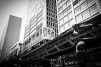 Chicago elevated L train with downtown Chicago buildings in black and white.