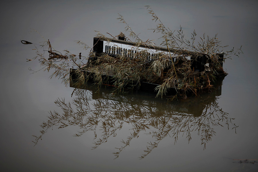 A piano is submerged in water in the area devastated by tsunami in Rikuzentakat March 21, 2011.   REUTERS/Damir Sagolj (JAPAN)