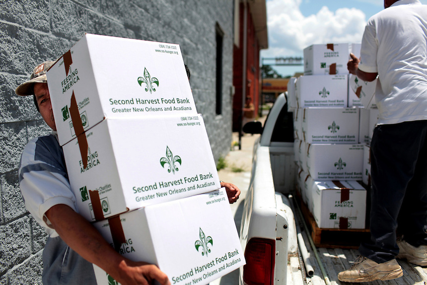 Phong Nguyen, (left) from Luling, LA, helps unload boxes of donated food from Second Harvest Food Bank with Catholic Charities after waiting for four hours for financial support in New Orleans East, LA on May 21, 2010. The Vietnamese fishing community have struggled to survive after the shrimping industry shut down three weeks earlier after the BP oil spill in the Gulf of Mexico.
