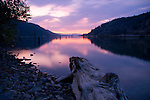 Idaho,North,Lake Coeur d'Alene, Wolf Lodge Bay. Pink and purple sky reflections in the calm waters with rustic pilings and driftwood.