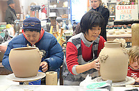 Santa Monica College art students Chi Miyamoto (left) and Mari Johnson work on their ceramics during the 6th Annual Santa Monica Airport Artwalk on Saturday, March 17, 2012.