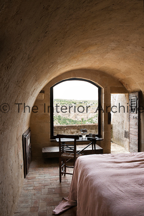 This bedroom opens up onto a small balcony with stunning views of the surrounding countryside at the Albergo Diffuso Le Grotte della Civita in Southern Italy housed in restored caves