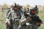 Pfc. Juan Rodriguez, 21, of San Juan, Puerto Rico, and Spc. Zachary Isakson, 22, of Madison, S.D., with Battery B, 15th Field Artillery Regiment, trudge through a field with other troops as they search for insurgents and weapons caches south of Mahmudiyah, Iraq. July 11, 2007. DREW BROWN/STARS AND STRIPES