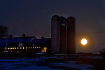 Goshen, New York - The full moon sets behind a farm on  March 16, 2014.