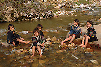 Children washing their feet and playing in river in Sapa, North Vietnam.