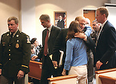 Prince William County (Virginia) Commonwealth Attorney Paul Ebert, second from right, gives a hug to Katrina Hannum, daughter of sniper victim Linda Franklin, after a jury found sniper suspect John Allen Muhammad guilty on four charges in courtroom 10 at the Virginia Beach Circuit Court in Virginia Beach, Virginia on November 17, 2003.<br /> Credit: Dave Ellis - Pool via CNP