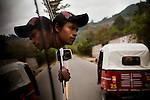 A minibus fare collector looks outside in the mountainous are of Nebaj, an indigenous town in the Ixil region, where thousands were massacred. They do not talk about the war. It was in this plaza where former military general Otto Perez Molina, now president, was based. He stationed soldiers in the bell-towers and forced men into civilian patrols - such as fathers, brothers, uncles, cousins, neighbors - and were often forced to kill suspecting guerillas, those very family members or friends they've known their whole life, during public executions in the plaza. Nebaj, Guatemala, on April 1, 2012.
