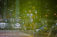 Reflection of Omar Masaad and Laurens Jan Anjema in the sidewall of the glass court at the quarterfinals of the 2010 US Open METROsquash championships held in Chicago, IL.