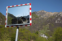 Switzerland. Canton Ticino. View on Corippo from the village San Bartolomeo, Vogorno. Traffic mirror for security and safety. Corippo lies in the Verzasca valley. Monte del Corgell is the mountain's name above the village. Corippo is the smallest municipality in Switzerland. Despite this, it possesses the trappings of communities many times its size such as its own coat of arms and a town council consisting of three local citizens. A town council is a democratically elected form of government for small municipalities. A council may serve as both the representative and executive branch. The village has maintained its status as an independent entity since its incorporation in 1822. 8.05.13 © 2013 Didier Ruef?.